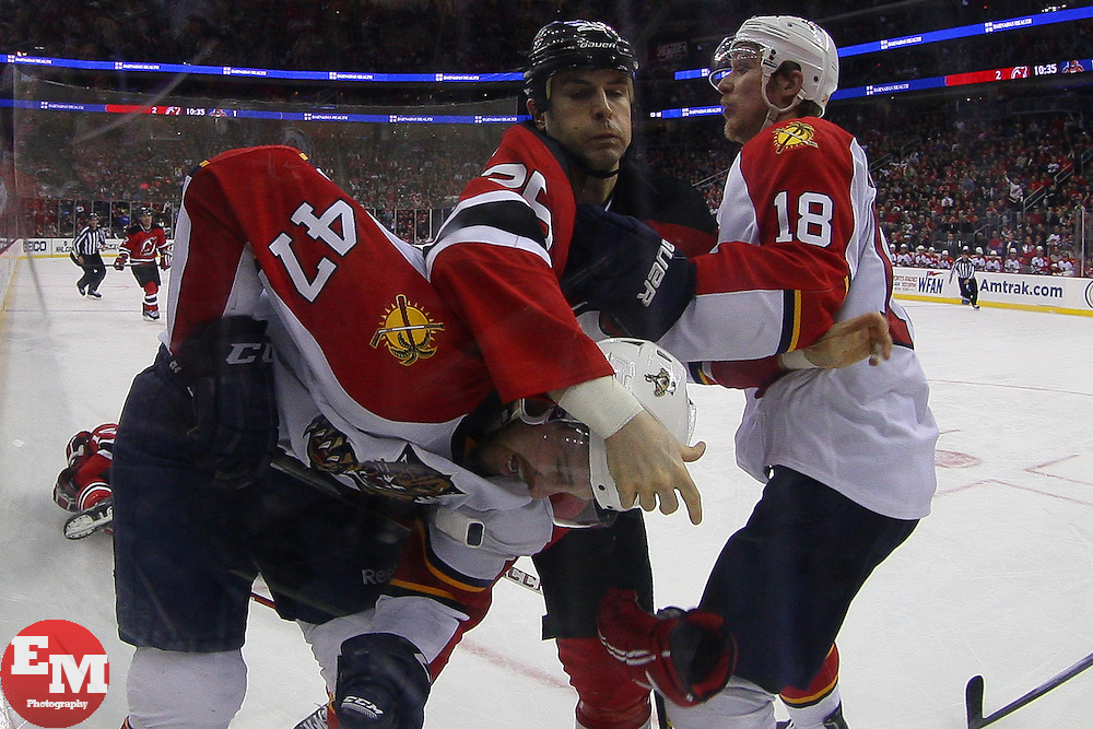 Mar 23, 2013; Newark, NJ, USA; New Jersey Devils right wing Tom Kostopoulos (25) punches Florida Panthers defenseman Colby Robak (47) after Robak cross-checked New Jersey Devils center Tim Sestito (15) during the third period at the Prudential Center. The Devils defeated the Panthers 2-1.