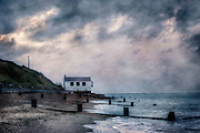 a cottage at the sea under a stormy sky