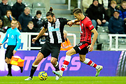 Andy Carroll (#7) of Newcastle United on the ball under pressure for Jan Bednarek (#35) of Southampton during the Premier League match between Newcastle United and Southampton at St. James's Park, Newcastle, England on 8 December 2019.