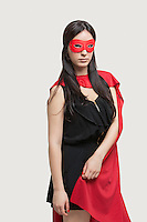 Portrait of young woman in superhero costume standing against gray background