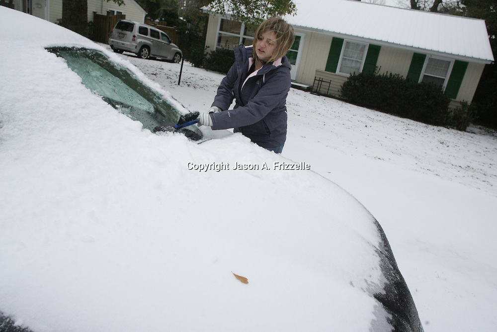 Sierra Cockrill clears snow and ice off her car on Rosemont Avenue in Wilmington, N.C. Wednesday January 29, 2014. Wilmington saw a wintry mix of sleet, snow, and freezing rain Tuesday and Wednesday which caused extensive closings throughout the area. (Jason A. Frizzelle)