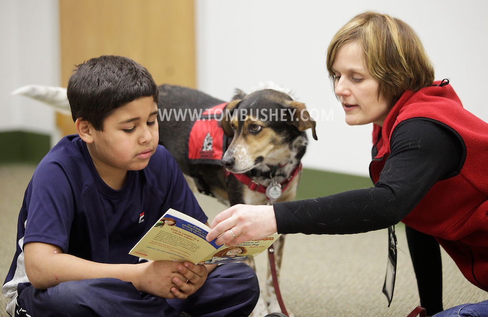 Janine Bixler, right, helps Chris Peralta, 8, read to her dog Milo during the FURacious reading program at Cornwall Library on Friday, Feb. 25, 2011. Bixler is an associate professor of education at Mount Saint Mary College in Newburgh.