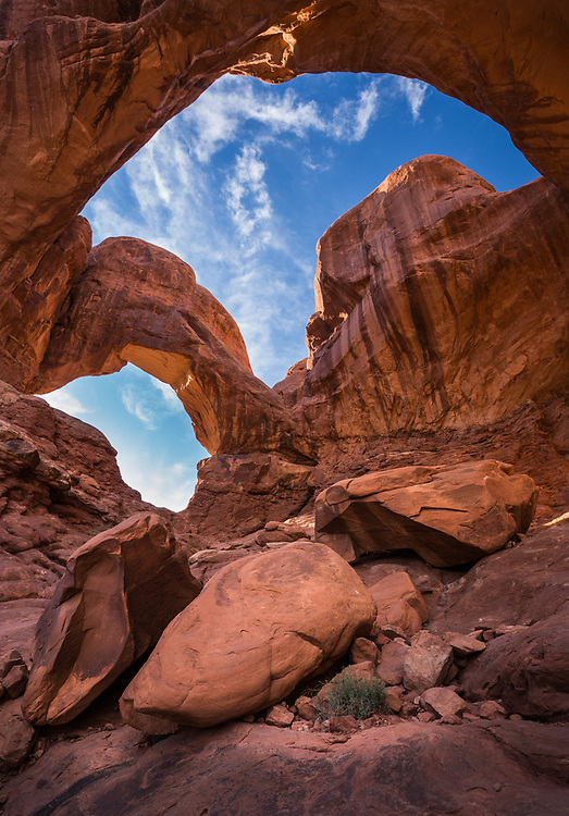 blue sky and whispy white clouds as seen through double arch in Arches National Park, Utah