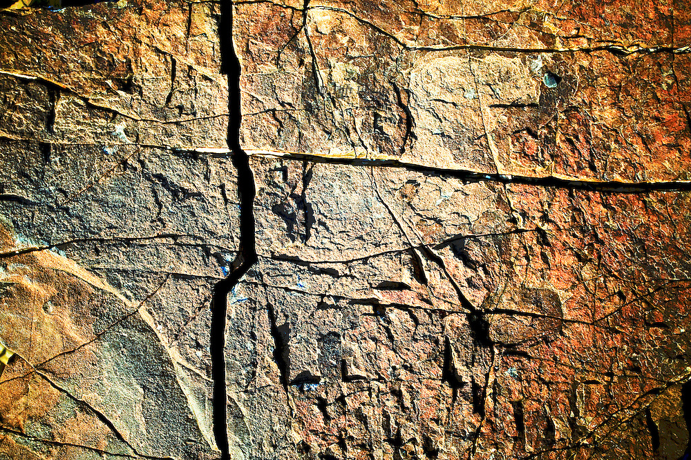 Detail of incised pattern in rock, Wadi El Ain, Oman.  Long-armed cross and an arc with varied textures and colors orange and silvery grey make an appealing design.  The colors and texture have been emphasized in post processing by targeted saturation and sharpening.