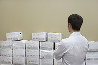 Business man standing in front of stack of filing boxes in storage room back view