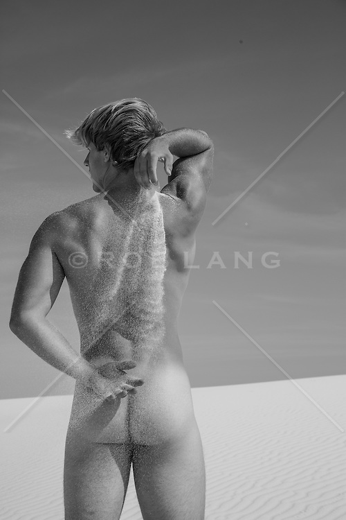 nude man pouring sand down his back in White Sands, NM
