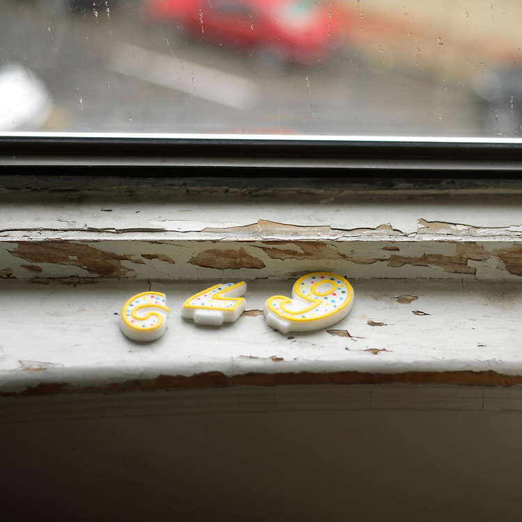 """29"" birthday candles on a window ledge looking onto the rainy street"