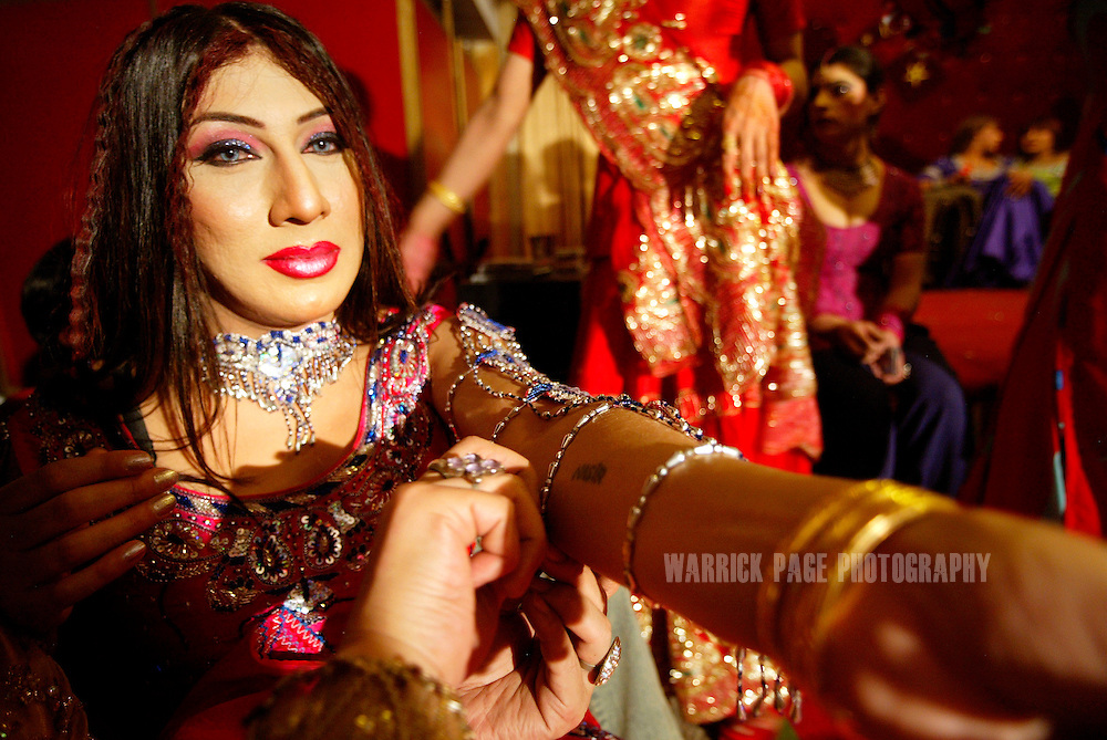 "A Hijra (eunuch), has his jewelry adjusted before a performance at an underground party, June 16, 2005, Rawalpindi, Pakistan. The suspected hideout of Osama Bin Laden, Al Qaeda leaders and countless Islamic militants, Pakistan is also home to one of the subcontinents largest communities of transsexuals, eunuchs and transvestites, or as they are more commonly known - Hijras. Caught between modernity and fundamentalism at the frontline in the war against terror, the Islamic Republic is a country at war with its own identity, yet its Kushras (Urdu for eunuch) stand out as a tight-nit community of devout Muslims. As Pakistan's most marginalised community, they live in fear ""24 hours a day"", according to the group She-male Rights of Pakistan. Hijras are considered by many as unclean, amoral, drug users, and who also have the ability to place curses. Many people fear their curse so gravely, they will give generously when a Kushra comes to beg in their neighbourhood and ask them for Allah's blessing.. (Photo by Warrick Page)"