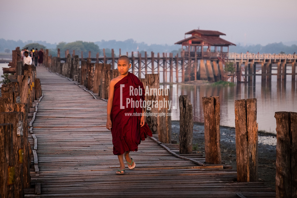 A young monk walks at sunrise across the wooden U Bein's Bridge near Amapura in Mandalay.