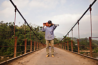 A young man with a chainsaw poses for a portrait on a suspension bridge in northern Vietnam.