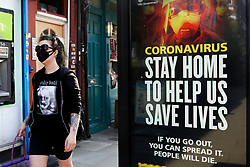 © Licensed to London News Pictures. 09/04/2020. London, UK. A woman wearing a face mask walks past a coronavirus public information campaign billboard in north London, which focuses 'STAY HOME TO HELP US SAVE LIVES.' © Licensed to London News Pictures. 09/04/2020. London, UK. A woman wearing a face mask looks at a coronavirus public information campaign billboard in north London, which says 'STAY HOME TO HELP US SAVE LIVES.' during the outbreak of the COVID-19 virus. Photo credit: Dinendra Haria/LNPduring a pandemic outbreak of the COVID-19. Photo credit: Dinendra Haria/LNP