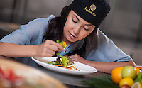 A young woman guest places the final touch on a salad during a culinary training lesson at Fivelements Healing Center. Resort photography by Djuna Ivereigh.
