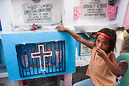 A child sits beside a baby's tomb in front of Rose Marie Ferrer's home, built over graves, in an inhabited cemetery in Paranaque City, Metro Manila, The Philippines on 18 January 2013. A candle, bought from Rose, burns on the tomb, after the deceased child's parents had come to remember the child on its birthday on 18 January 2004. Photo by Suzanne Lee for Save the Children UK