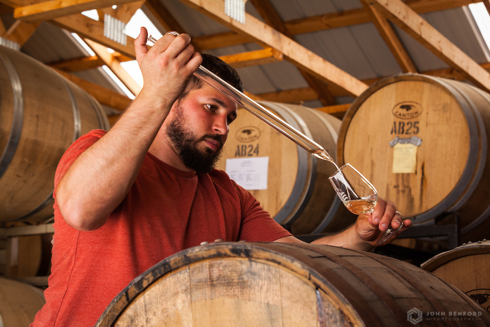 "A distiller uses a ""whiskey thief"" to pour a sample of aged spirits into a glass."