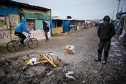 © Licensed to London News Pictures. 24/10/2016. Calais, France. Migrants walk past a burnt out fire as the evacuation and demolition begins at the migrant camp in Calais, known as the 'Jungle'. French authorities have given an eviction order to thousands of refugees and migrants living at the makeshift living area of the French coast. Photo credit: Ben Cawthra/LNP