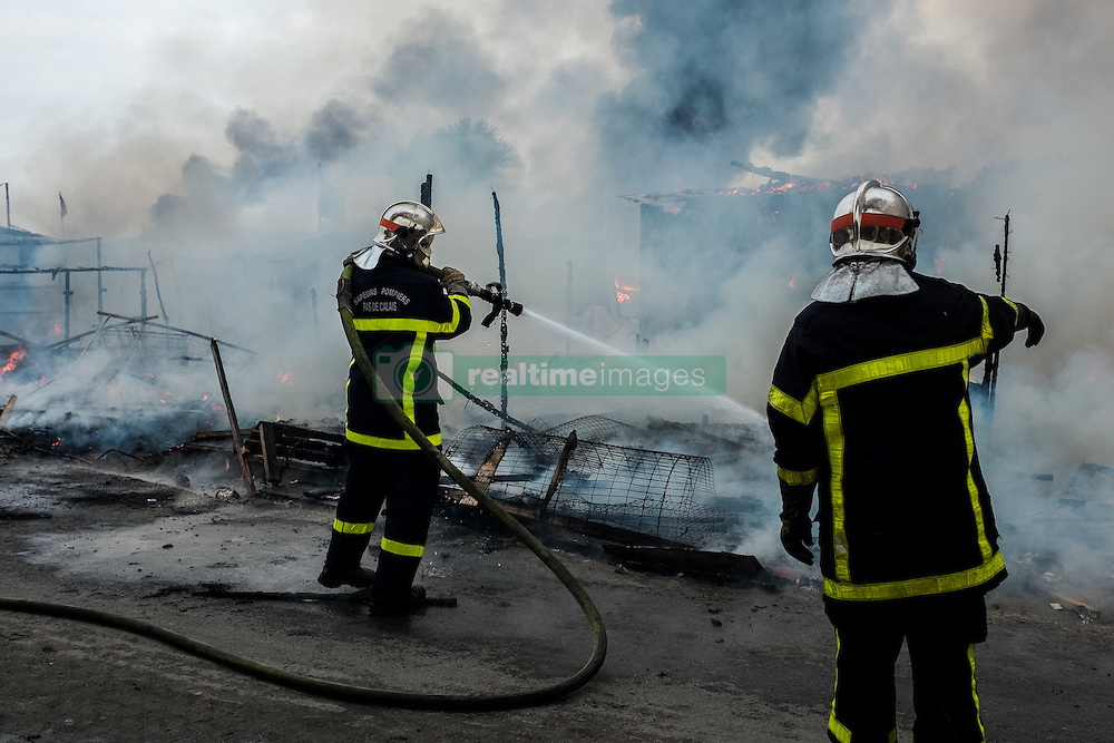 October 26, 2016 - Calais, France - Firefighter extinguish in the Calais Jungle a burning hut, on October 26, 2016. Huge fires destroyed a mayor part of the refugee camp today. (Credit Image: © Markus Heine/NurPhoto via ZUMA Press)