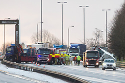 "© Licensed to London News Pictures. 01/12/2017. Bramham, UK. Picture shows the scene of a multiple vehicle incident on the north bound carriageway of the A1M near Bramham in Yorkshire that has left a lorry hanging over the edge of a bridge. A number of collisions have already been reported as snowfall through the night, coupled with freezing temperatures affected the region's roads. At around 7am, Highways England reported that two lanes were blocked on the A1 northbound within junction 44 due to a collision between multiple vehicles. A spokesperson for the agency said: ""Emergency services at scene, please take care on approach, delays are building. Photo credit: Andrew McCaren/LNP"