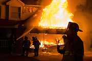 Firefighters attempt to extinguish a garage fire on Watchman Court in Rochester, New York.