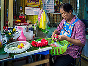 17 SEPTEMBER 2018 - BANGKOK, THAILAND: A woman makes and sells flower garlands from a small shop in Klong San market, next to the ICONSIAM development. ICONSIAM is a mixed-use development on the Thonburi side of the Chao Phraya River. It is expected to open in 2018 and will include two large malls, with more than 520,000 square meters of retail space, an amusement park, two residential towers and a riverside park. It is the first large scale high end development on the Thonburi side of the river and will feature the first Apple Store in Thailand and the first Takashimaya department store in Thailand. Rents for shopkeepers in Klong San market can be up to 30,000 Thai Baht per month (about $920US) and some in Bangkok are concerned that Klong San Market will lose its local character when the huge mall opens.    PHOTO BY JACK KURTZ