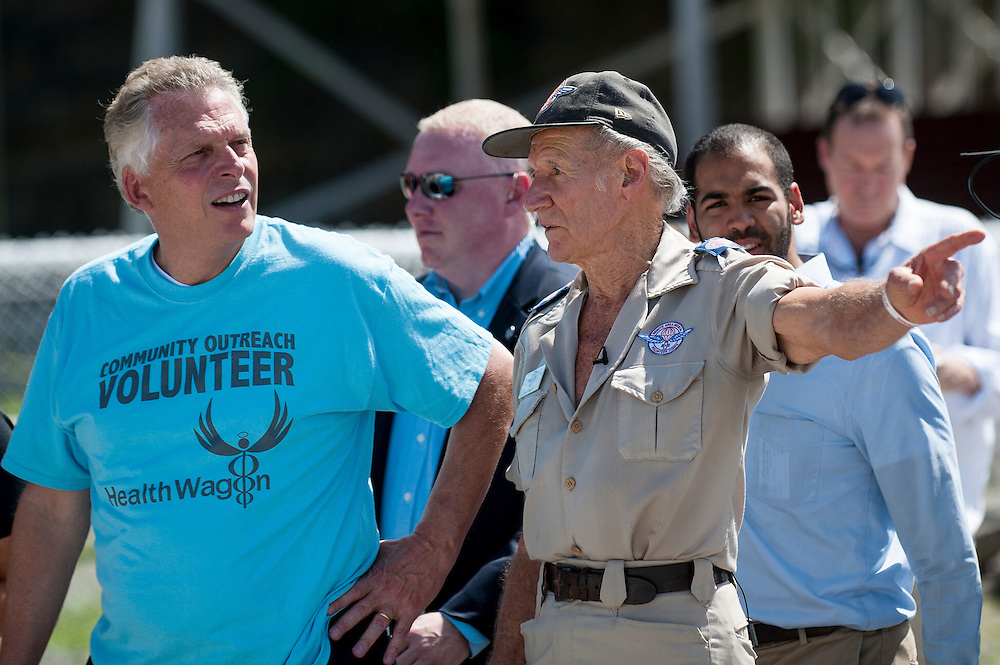 RAM Founder Stan Brock, left, gives Virginia Governor Terry McAuliffe, left, a tour at the16th annual Remote Area Medical (RAM), clinic in Wise, Virginia, U.S., on Friday, July 17, 2015. RAM is a nonprofit that delivers free medical care to people living in rural areas. On RAM's first day it took in over 1,600 patients, setting an opening day record. By noon on Saturday, RAM had taken in another 1,000 patients. One woman's life may have been saved on Friday after women's health physicians determined she had a dangerous ectopic (tubal) pregnancy. She was taken to an area hospital for further care. In recent years, 2,500 to 3,000 people have sought care at this clinic at the fairgrounds. Photographer: Pete Marovich/Bloomberg