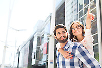 Smiling woman pointing away while enjoying piggyback ride on man in city