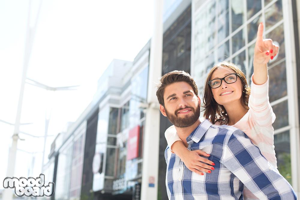 Smiling woman pointing away while enjoying piggyback ride on man in city