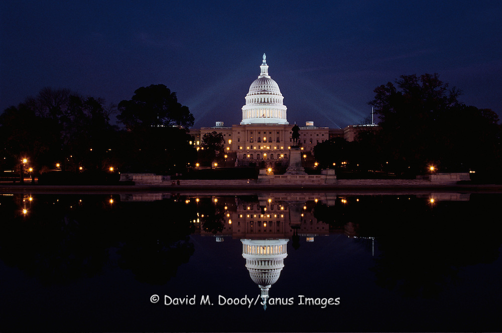 The US Capitol at night reflected in the pool at the foot of Capitol Hill, Washington DC.