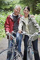 Portrait of senior man and middle-aged woman on bicycles in forest smiling
