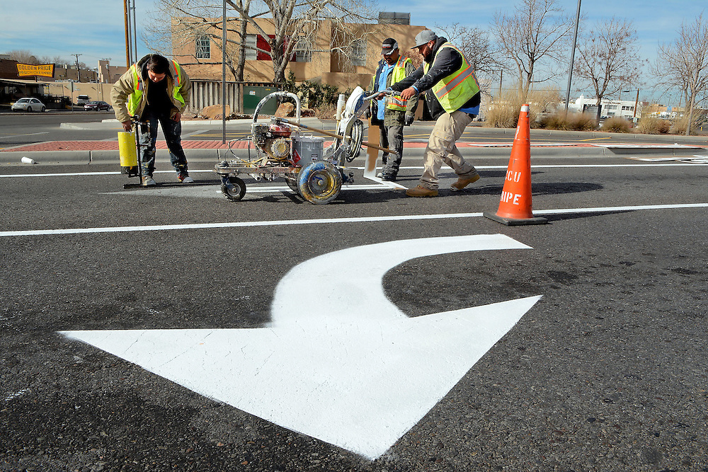 jt123016c/a sec/jim thompson/  left to right Marcus Martinez spreads glass beads for reflective purposes, Omar Caro moves the stencils and Jeremy Baca runs the spray painter as they  paint Yale near the corner of Lomas near UNMH Friday afternoon.  Friday Dec. 30, 2016. (Jim Thompson/Albuquerque Journal)