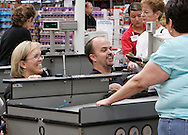 Chris Kotzian (R) and wife Barb (L) check out at a store in Thornton, Colorado March 25, 2010.  Both about four-feet-tall,  the Kotzians are achondroplasia dwarfs, a rare genetic disorder of bone growth.  Preferring to be referred to as little people their parents are average size. They have a daughter that is average size and a son who is also a little person.  REUTERS/Rick Wilking (UNITED STATES)