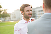 Businessman conversing with colleague at park on sunny day