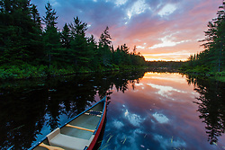 A canoe at sunrise on Little Berry Pond in Maine's Northern Forest. Cold Stream watershed, Johnson Mountain Township.