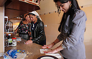 Romania, Tirgu Jiu. Wife and daughters of Ninel Potirca - one of the wealthiest ROMa people in Romania - preparing the meal at their home's kitchen. All generations of Potirca family are living together in 3 mansions, sharing a common yard.