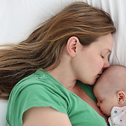 A newborn baby is cuddled by her mother while asleep. Photo Tim Clayton