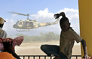 Young Haitian boy avoids helicopter rotor dust as Brigadier General Juan Manuel Mendez' helicopter lifts off from the Love a Child Health Center in Fond Parisien, Haiti on Wednesday, January 27, 2010. Brig. Gen. Mendez is the Commander of the Emergency Operation Center of the Dominican Republic. An Operation Smile orthopedic and plastic surgical team from Penn State University - Hershey Medical Center in Hershey, PA are in Haiti treating victims of the 7.0 earthquake earlier this month.