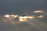 Darling Harbour. Qantas Boeing 747 jumbo jet flying in front of sunset.