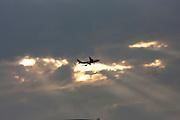 Darling Harbour. Qantas Boeing 747 jumbo jet flying in front of sunset.