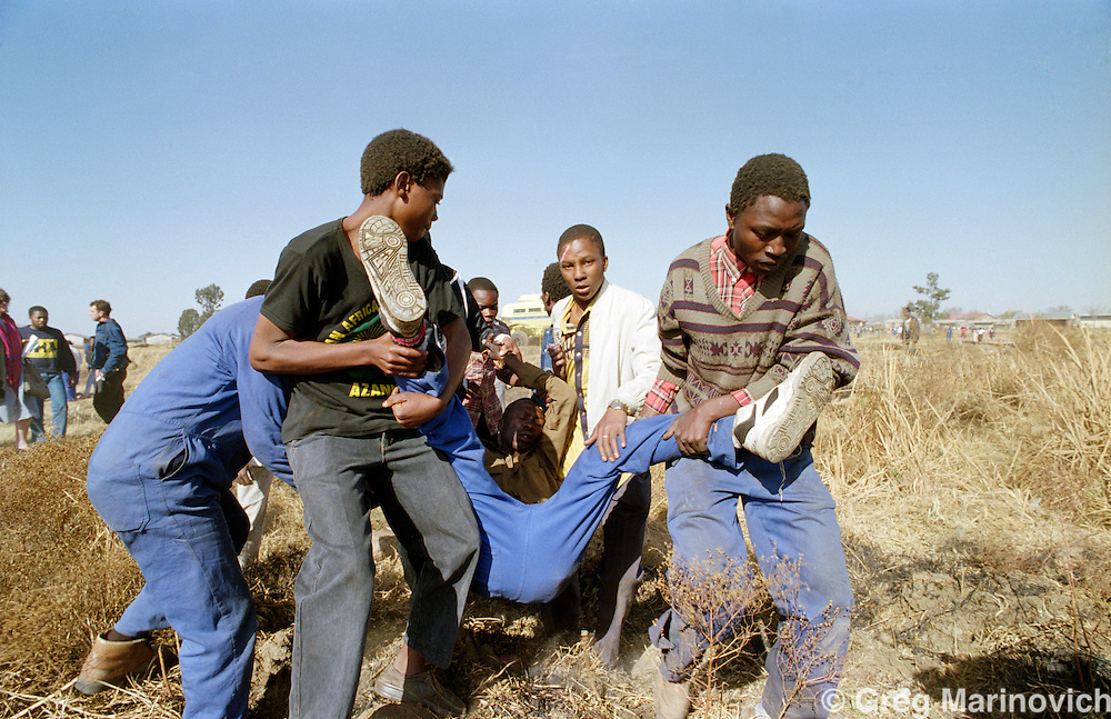 Boipatong, Vaal, Transvaal, South Africa 1992, June. ANC supporters carry wounded as police and ANC self defence units exchange fire in the aftermath of President FW de Klerks visit several days after the killing of 41 people by Inkatha warriors said to be supported by police.