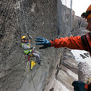 "Rope access technicians Haukur Grönli and Atli Þór Þorgeirsson working on the removal of safety nets, in the canyon ""Hafrahvammagljúfur"", at Kárahnjúkar dam area, Iceland. Safety nets were put up to prevent rockfall onto workers, working on the lower dam."