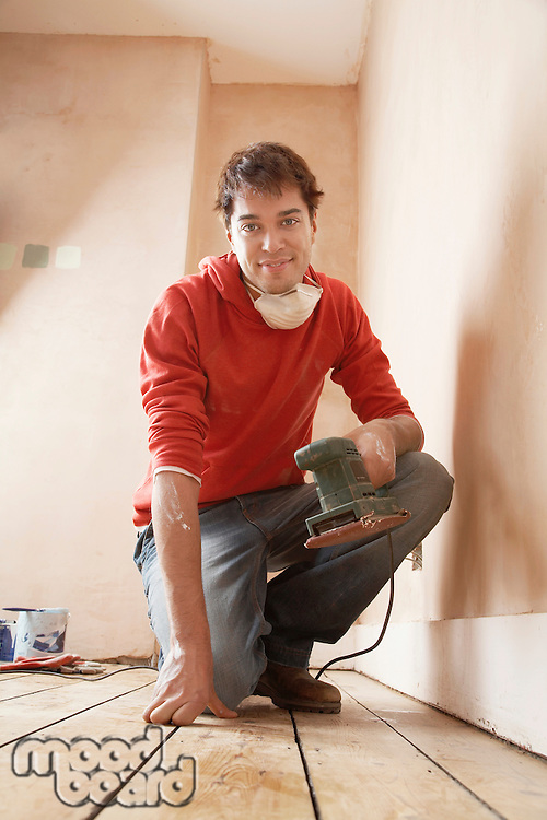 Man holding sanding tool  in unrenovated room portrait