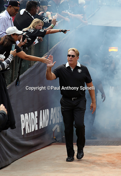 Oakland Raiders head coach Jack Del Rio high fives a fan as he comes onto the field for the 2015 NFL week 1 regular season football game against the Cincinnati Bengals on Sunday, Sept. 13, 2015 in Oakland, Calif. The Bengals won the game 33-13. (©Paul Anthony Spinelli)