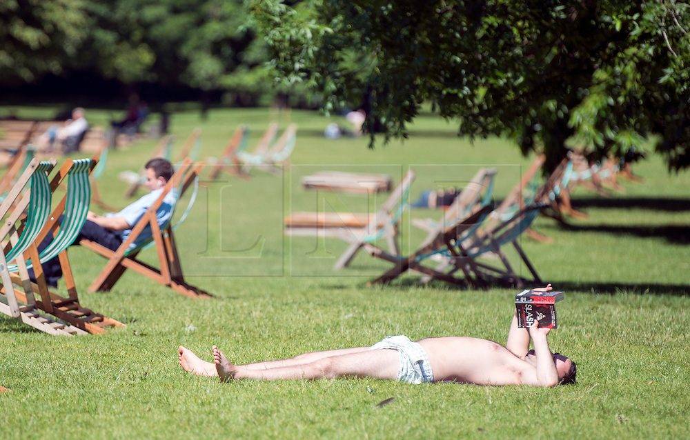 © Licensed to London News Pictures. 10/06/2014. London, UK. A man relaxes in Hyde Park.  Londoners enjoy the sunny weather today 10th June 2014. Photo credit : Stephen Simpson/LNP