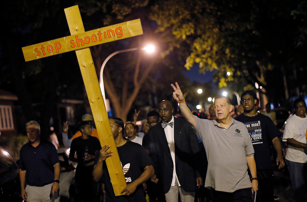 Father Michael Pfleger (3rd R) marches  through the streets of a South Side neighborhood during a weekly night-time peace demonstration in Chicago, Illinois, September 16, 2016. REUTERS/Jim Young