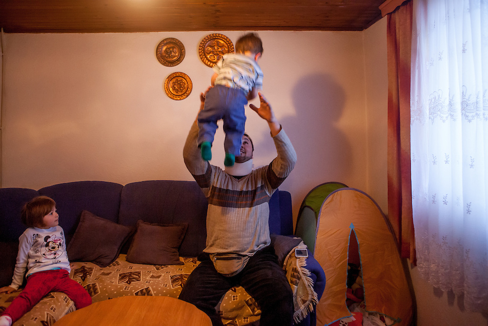 Former refugee Elvis Causevic playing with his son Aldin (1 1/2) watched by daughter Adna (3 1/2) in the living room at the  families house in Hadžići . The family settled here after the war ended in Bosnia. Hadžići is a town and a municipality located about 20 km south west of Sarajevo city but within the Sarajevo Canton of Bosnia and Herzegovina. According to the census of 2013, Hadžići municipality has a population of 23,891 residents.
