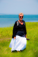 A beautiful portrait photo of a lady standing in a green field with the sea as a background.