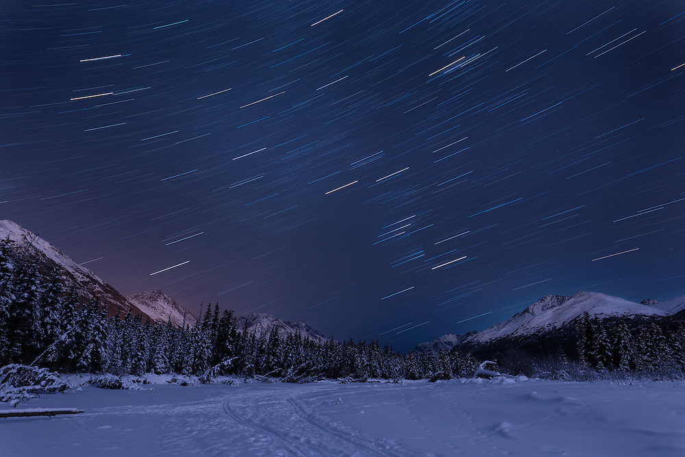 Long exposure of night skies above Chugach Mountains and Eagle River Valley in Southcentral Alaska. Winter. Evening.