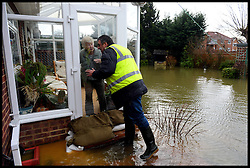 Community workers help an old lady to build up sand bangs at her back door in Wraysbury as it floods. Parts of the UK continues to be flooded in certain areas, Wraysbury, United Kingdom, Tuesday, 11th February 2014. Picture by Andrew Parsons / i-Images