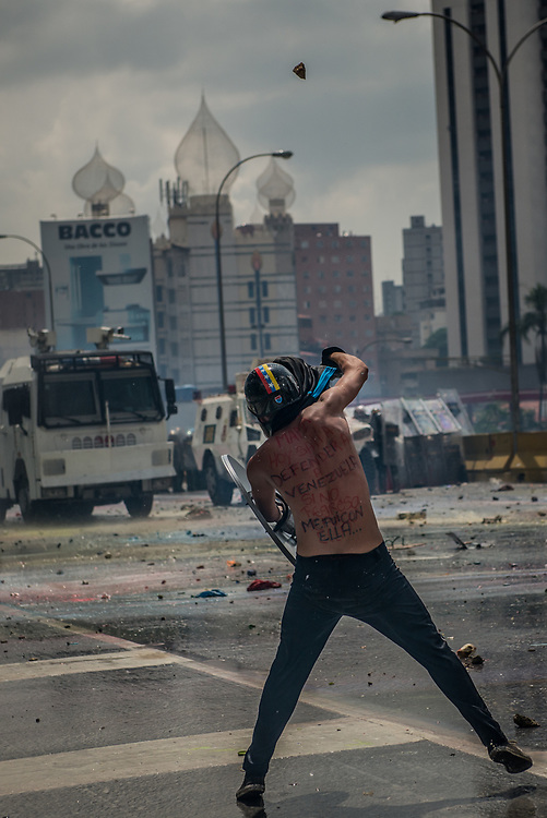 "CARACAS, VENEZUELA - MAY 10, 2017:  An anti-government protester with a message written on his back in Spanish, that says: ""Mom, today I went to defend Venezuela - if I don't return, I went with her...""  throws stones during clashes for control of the Francisco Fajardo highway with members of the National Police, who responded with a water cannon, and by heavily tear gassing and firing rubber bullets and buckshot at protesters.  The streets of Caracas and other cities across Venezuela have been filled with tens of thousands of demonstrators for nearly 100 days of massive protests, held since April 1st. Protesters are enraged at the government for becoming an increasingly repressive, authoritarian regime that has delayed elections, used armed government loyalist to threaten dissidents, called for the Constitution to be re-written to favor them, jailed and tortured protesters and members of the political opposition, and whose corruption and failed economic policy has caused the current economic crisis that has led to widespread food and medicine shortages across the country.  Independent local media report nearly 100 people have been killed during protests and protest-related riots and looting.  The government currently only officially reports 75 deaths.  Over 2,000 people have been injured, and over 3,000 protesters have been detained by authorities.  PHOTO: Meridith Kohut"