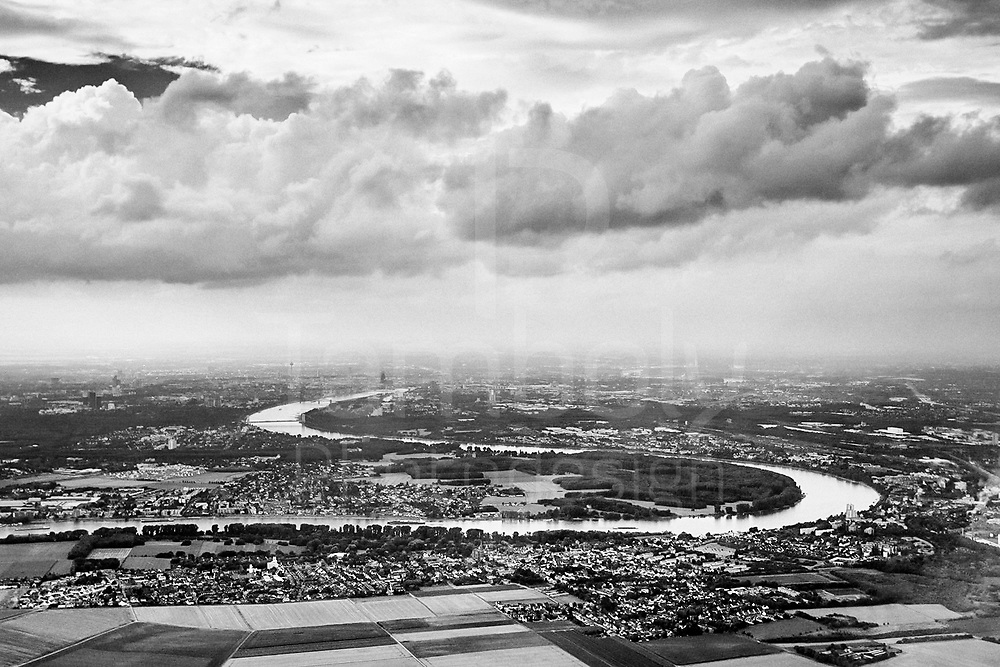A black and white aerial photo of the curvy rhine river crossing the city of Cologne in a gray day with a cloudy sky