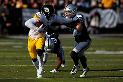 OAKLAND, CA - DECEMBER 09: Wide receiver JuJu Smith-Schuster #19 of the Pittsburgh Steelers stiff arms safety Erik Harris #25 of the Oakland Raiders during the second quarter at the Oakland Coliseum on December 9, 2018 in Oakland, California. The Oakland Raiders defeated the Pittsburgh Steelers 24-21. (Photo by Jason O. Watson/Getty Images) *** Local Caption *** JuJu Smith-Schuster; Erik Harris